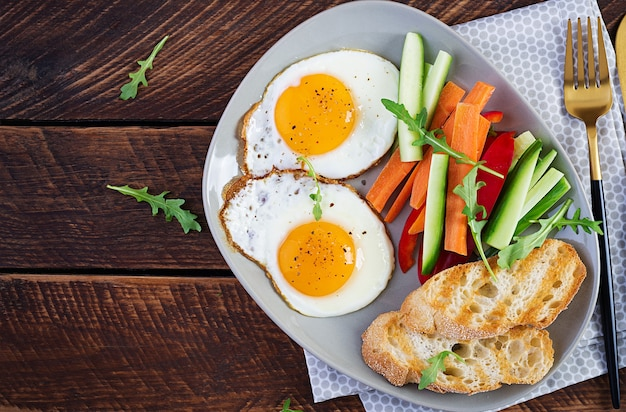 Breakfast. fried eggs with fresh carrot and cucumber