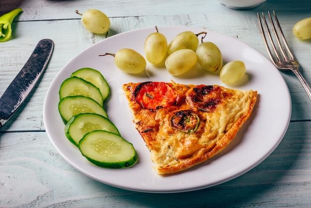 Завтрак фриттата с нарезанным огурцом и зеленым виноградом на белой тарелке над деревянным столом.