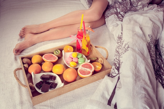 Breakfast from fruits to bed and female legs