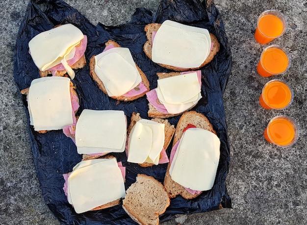 Завтрак из бутербродов и сока на свежем воздухе