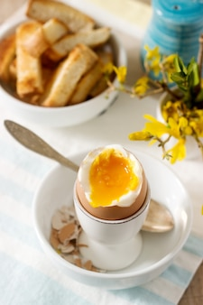 Breakfast from soft-boiled egg, bread toast, coffee with cream and fresh newspaper.