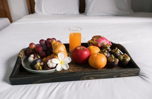흰색 침대 시트에 검은 나무 쟁반에 아침 과일 크루아상 오렌지 주스 건강 식품