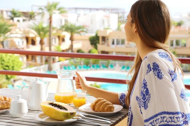 彼女の休暇のリゾートホテルでブランチを食べる朝食の女の子