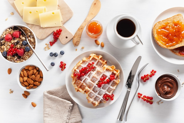 Breakfast granola berry nuts, waffle, toast, jam, chocolate spread and coffee. top view