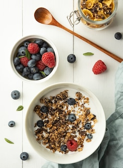 Завтрак мюсли с молоком черника малина кукурузные хлопья вид сверху дерево