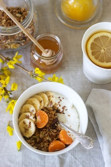 Breakfast of granola with yogurt and tea and forsythia flowers on a linen tablecloth. rustic style.