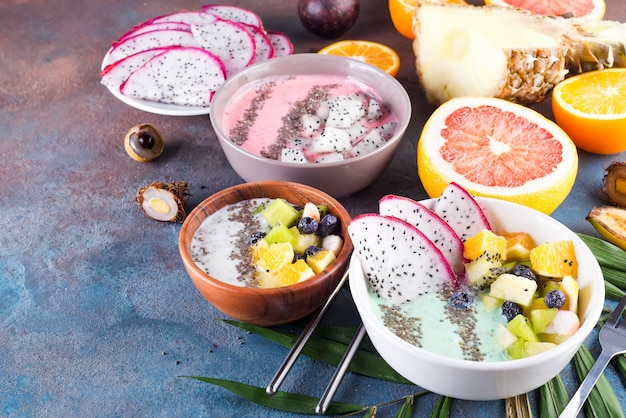 Breakfast green yoghurt bowl topped with pitaya, pineapple, chia seeds and berries with palm leaf on stone background, top view