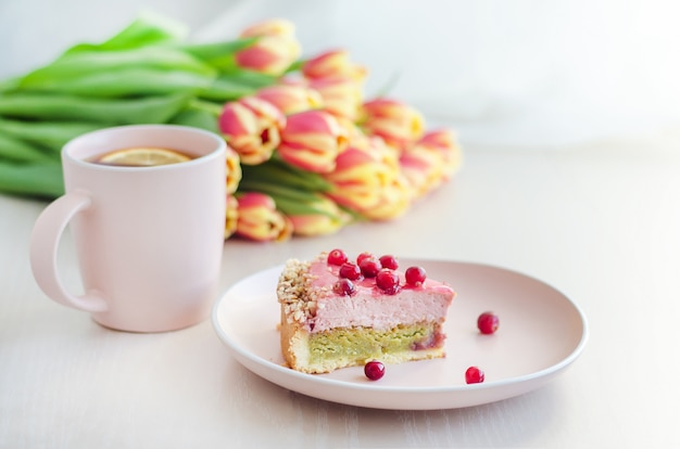 Breakfast, holiday, morning with flowers tulips, cake, tea in pink mug on white