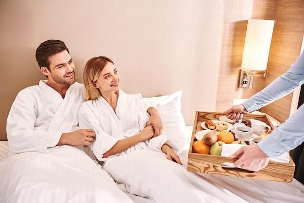 ベッドでの朝食。カップルは一緒にホテルの部屋のベッドで抱きしめています。ラブストーリー。ウェイターはカップルに朝食を持ってきます