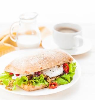 白い木の表面で素朴なスタイルの朝食。ポーチドエッグとグレインマスタードのチャバタとホットコーヒーとフレッシュ