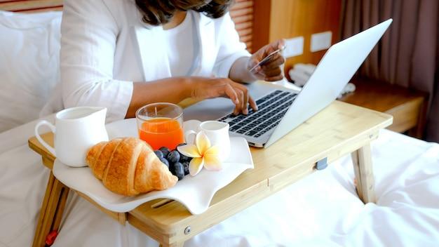 노트북을 사용하는 아시아 사업가 여행자 앞에 고급 호텔 방에있는 침대에 쟁반에있는 아침 식사.