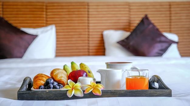 Завтрак в подносе на кровати в роскошном гостиничном номере, готовом к туристическому путешествию.