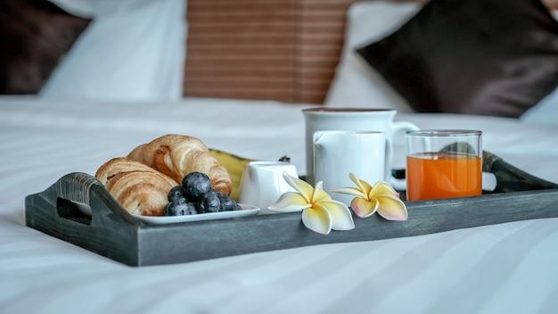 고급 호텔 객실 침대 위의 쟁반에서 아침 식사