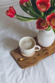 ベッドでの朝食。コーヒーのマグカップ、花瓶にチューリップの花束、木製のトレイ。女性の日。春。居心地の良い。