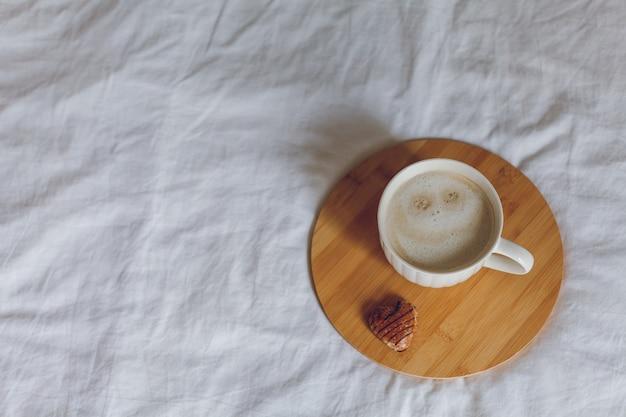 ベッドでの朝食。コーヒーのマグカップ、ハート型のクッキー、木製のトレイ。女性の日。居心地の良い。