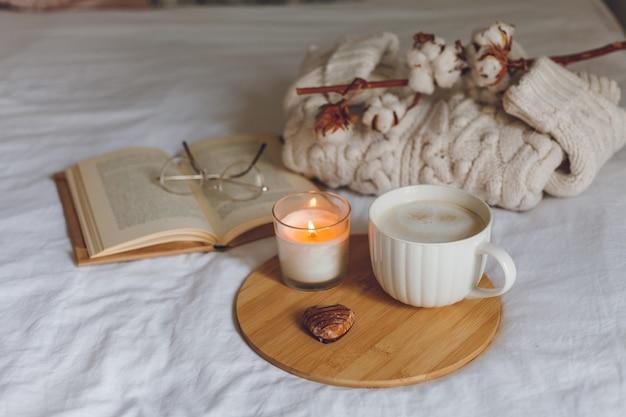 ベッドでの朝食。コーヒーマグ、ハート型のクッキー、本、グラス、キャンドル、木製トレイ。女性の日。居心地の良い。