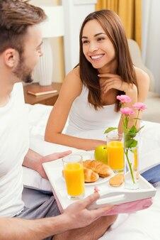 침대에서 아침 식사. 침대에서 아침 식사로 아내를 놀라게 하는 잘생긴 젊은 남자