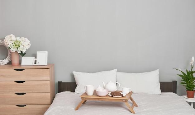 Завтрак в постель в гостиничном номере. проживание. завтрак в постель с чашкой чая с блинами на подносе на кровати