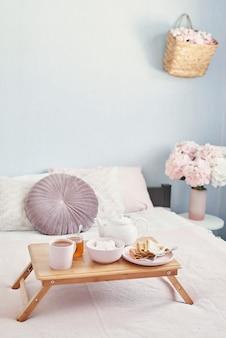 ホテルの部屋でベッドで朝食。宿泊施設。ベッドの上のトレイにパンケーキとティーカップとベッドで朝食します。