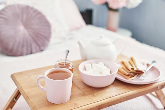 ホテルの部屋でベッドで朝食。宿泊施設。トレイにパンケーキとティーカップとベッドで朝食します。