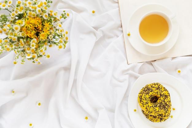 Завтрак в постель, чай с желтыми пончиками и букет ромашек.