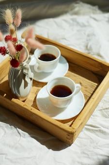 Завтрак в постели, попробуйте две чашки кофе и цветок при солнечном свете дома, горничная приносит поднос с завтраком в гостиничном номере, хорошее обслуживание