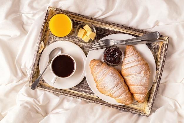 コーヒーとクロワッサンが付いているベッドでの朝食