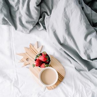 コーヒー マグカップとイチゴのベッドで朝食。明るいグレーのリネン。フラット レイアウト、トップ ビュー。
