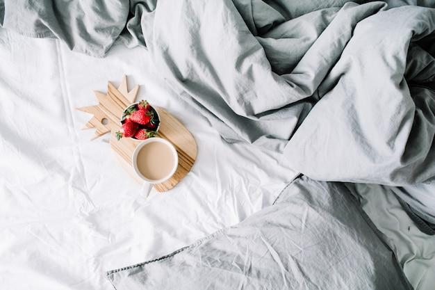 コーヒー マグカップとイチゴのベッドで朝食