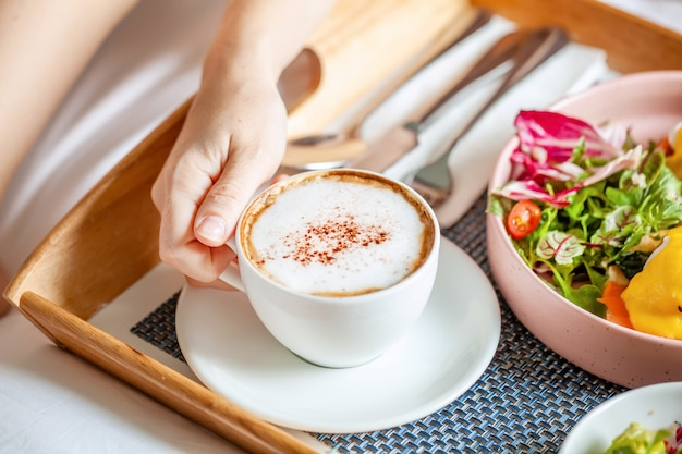 コーヒー、オレンジジュース、サラダ、果物、卵のベネディクトと一緒にベッドでの朝食