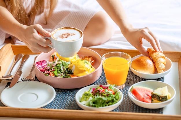 コーヒー、オレンジジュース、サラダ、果物、卵のベネディクトとベッドでの朝食