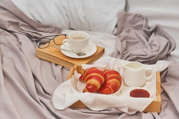 Завтрак в постель с эспрессо, цветком и круассаном