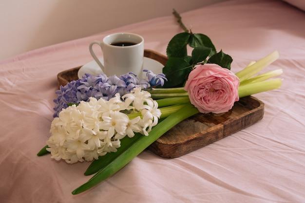 침대에서 따뜻한 커피와 신선한 꽃 장미와 나무 쟁반에 히아신스를 곁들인 아침 식사