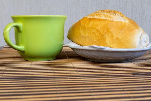 전통적인 프랑스 빵, 전통적인 브라질 빵, 녹색 컵으로 구성된 브라질에서의 아침 식사
