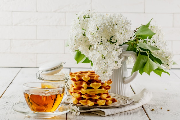 Завтрак в кафе - бельгийские вафли с соусом и чашка чая на деревянном столе в номере