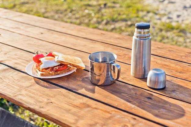 Завтрак на природе яичница с жареными тостами из бекона и горячим кофе из термоса