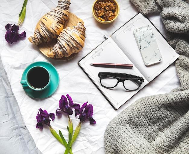 Завтрак в постель. утро, круассан, кофе, цветы и блокнот с ручкой. планирование