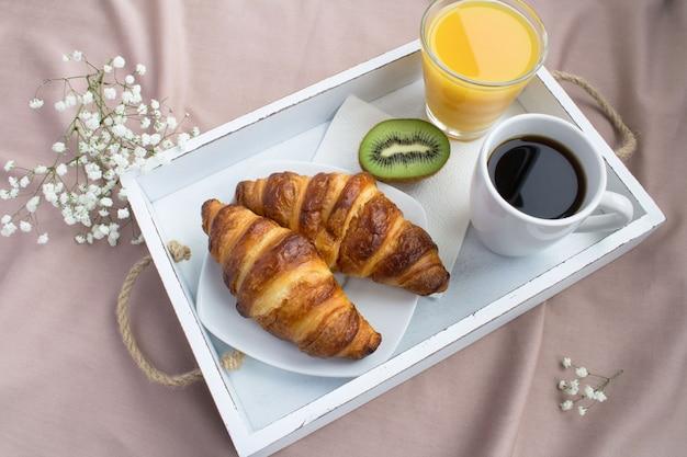 白い木製トレイのベッドでの朝食。上からの眺め。