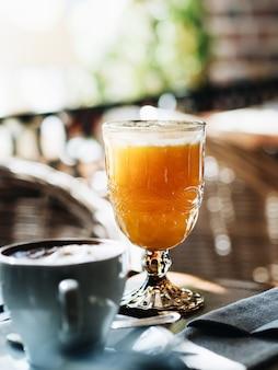 カフェで朝食。カプチーノとフレッシュジュースのカップ