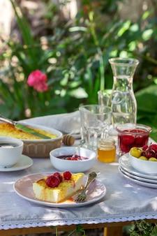 Завтрак в саду из запеканок, ягод, соусов и напитков. деревенский стиль.