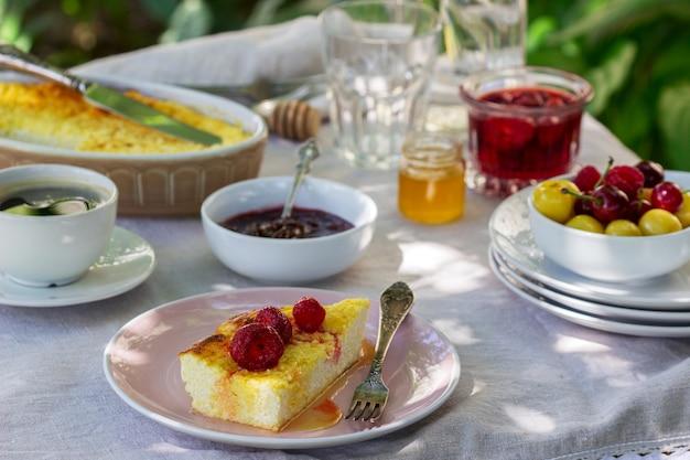 Завтрак в саду из запеканок, ягод, соусов и напитков.