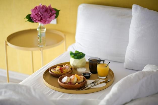 ホテルでの朝食。花とベッドで朝食。ベッドでコーヒー、ジュース、チーズケーキ。ベッドで食べる。怠けた週末。