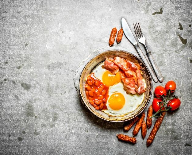朝の朝食。ベーコン、目玉焼き、豆、オレンジジュース。石のテーブルの上。