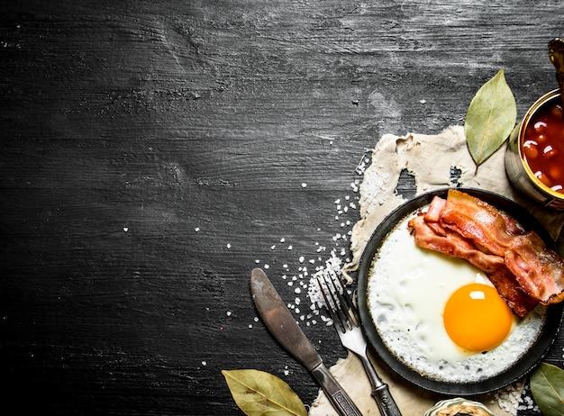 朝の朝食。目玉焼きとベーコンの豆。黒い木製の背景に。