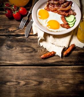 朝の朝食。ベーコンと卵とオレンジジュースの炒め物。木製のテーブルの上。
