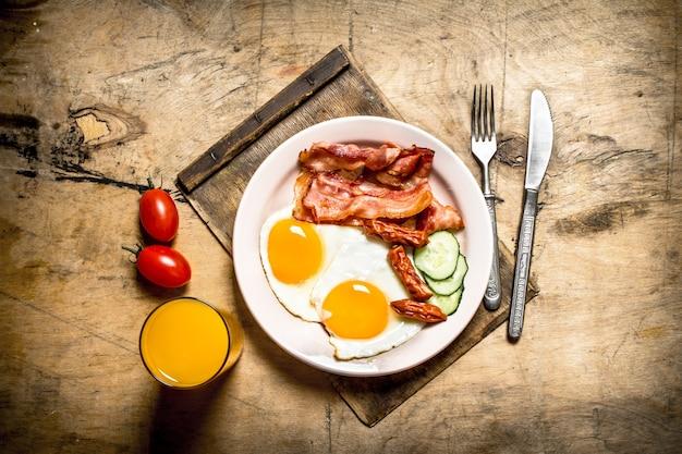 Утром завтрак. жареный бекон с яйцами и апельсиновым соком. на деревянном столе.