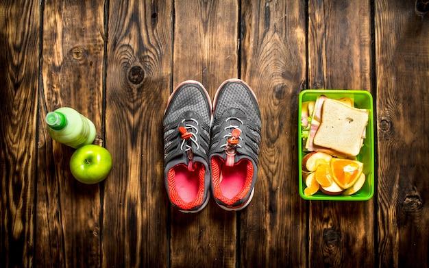 Утром завтрак. бутерброды, фрукты, молочный коктейль и спортивные кроссовки