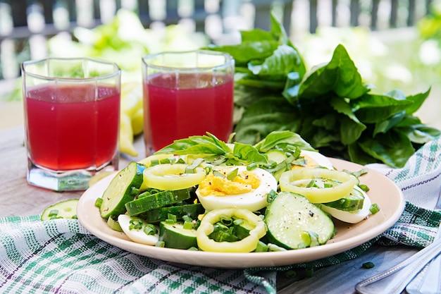 Завтрак в летнем саду. салат из яиц и огурцов с зеленым луком и базиликом.