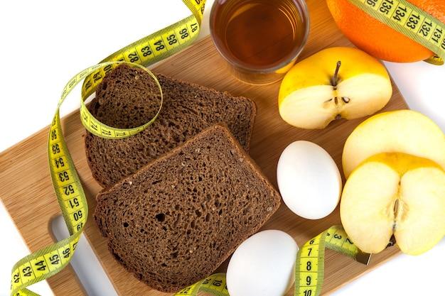木の板にパン、卵、オレンジ、リンゴジュースを含む朝食。測定値は白で隔離されています。ダイエットとボディケアの概念