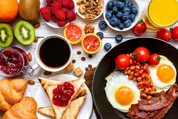 Breakfast including coffee, fried egg, bacon, beans, toast, croissant, orange juice with fruits and berries.